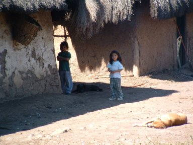 Curious girls in front of mud hut home